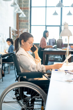 Female in wheelchair looking through paper and talking to client on smartphone