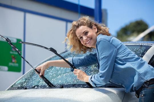woman putting wipers forward to wash car windscreen
