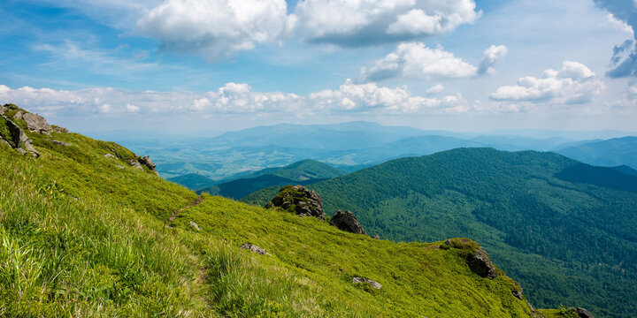 view from pikui mountain. huge stones on the grassy slopes. summer landscape of carpathian mountains. borzhava ridge in the distancee beneath a sky with clouds