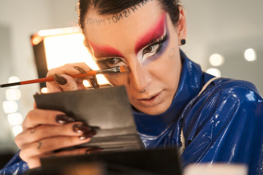 Drag queen looking at the hand mirror and applying makeup at his face