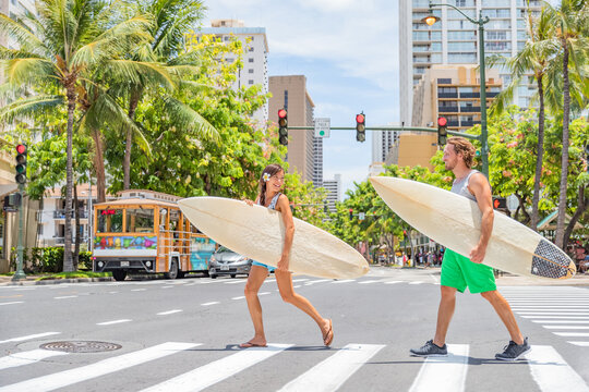 Honolulu Hawaii surfers couple tourists people walking crossing city street carrying surfboards going to the beach surfing. Surf living lifestyle. Surfer woman and man friends in Waikiki, Oahu, USA.