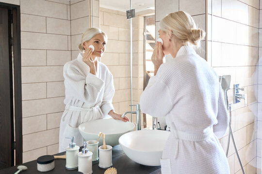Senior mature older caucasian woman cleansing face with cotton pad removing makeup looking at mirror wearing bathrobe. Everyday routine, anti wrinkle prevention skin care products concept.