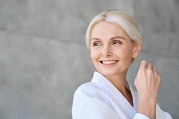 Obraz Headshot of happy smiling gorgeous middle aged woman wearing bathrobe at spa salon hotel looking away. Advertising of bodycare spa procedures antiage dry skin care products concept. - fototapety do salonu