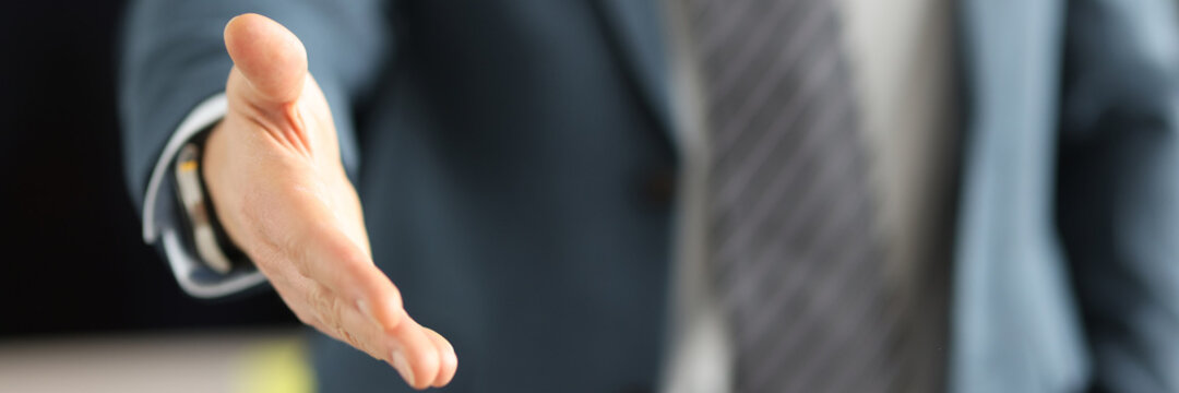 Man in business suit giving his hand for handshake closeup