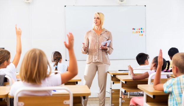 Woman teacher explaining studying material to tweens during lesson in elementary school,
