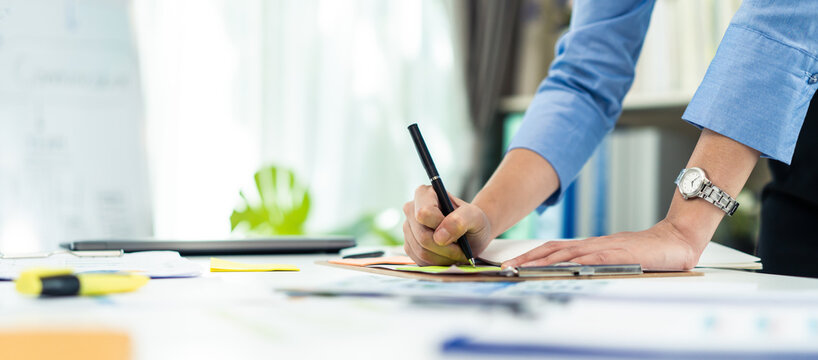 Hand of Businesswoman work in office write paperwork on table with pen