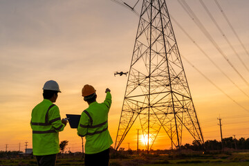 Fototapeta Team work of Engineers location help Technician use drone to flying inspect equipment instead of workers at the high voltage electric transmission tower, electric power station obraz