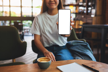 Fototapeta Mockup image of a beautiful woman showing a mobile phone with blank white screen obraz