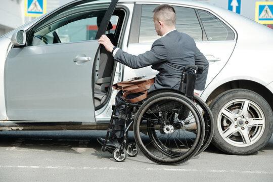 Businessman in wheelchair opening door of his car in urban environment