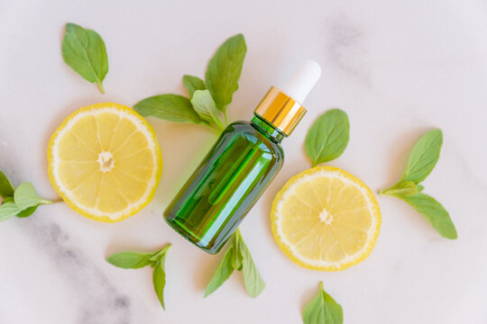 Serum with vitamin C. Lemon essential oil. Green glass bottle with a pipette, slices of lemon with mint leaves on a marble background. Health and beauty concept. Organic Natural Cosmetics