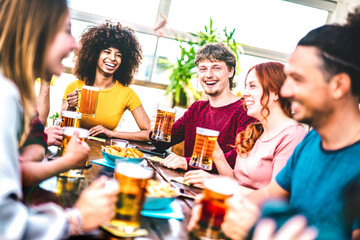 Obraz Young people toasting beer at brewery bar rooftop - Friendship life style concept with young milenial people enjoying happy hour time together at penthouse terrace pub - fototapety do salonu