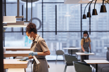 Fototapeta Side view portrait of young woman wearing mask while cleaning tables in modern restaurant interior, copy space obraz