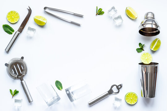 Flat lay of cocktail bar utensils and ingredietns - shaker, lime and ice