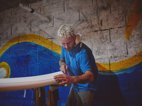 Man with equipment measuring surf board
