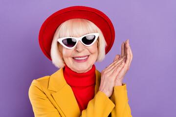 Fototapeta Portait of positive short hairdo aged lady hold hands wear yellow jacket cap eyewear isolated on purple background obraz