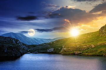 Fototapeta day and night time change concept above summer landscape with lake on high altitude. beautiful scenery of fagaras mountain ridge. open view in to the distant peak beneath a clouds with sun and moon obraz