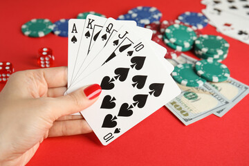 Fototapeta Woman holding playing cards with royal flush combination at red table, closeup obraz