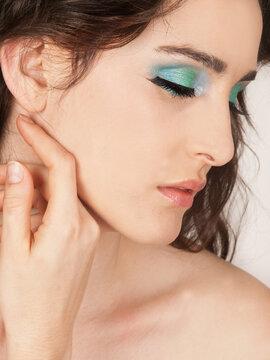 Retrato de mujer joven y bella mirando hacia un costado con la mano sobre el menton. Vista de frente y de cerca. Concepto: Beauty