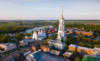 Aerial view of Shuya Orthodox Resurrection cathedral and bell tower on background with Teza River and cityscape, Russia.. - fototapety na wymiar