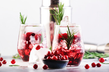 Obraz Cranberry, vodka, gin alcoholic cocktail with ice, rosemary and berries in tumbler glass. Summer long drink. Gray table background - fototapety do salonu