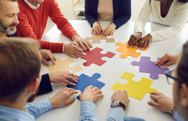 Fototapeta Collaboration concept. Diverse multiethnic people group team assembling jigsaw putting puzzle pieces together sitting at round office desk table represent team support during coaching training obraz