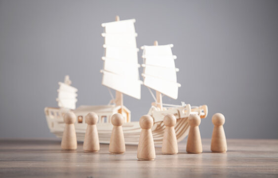 Wooden toy ship and human wooden figures. Leader. Teamwork. Partnership. Human resource