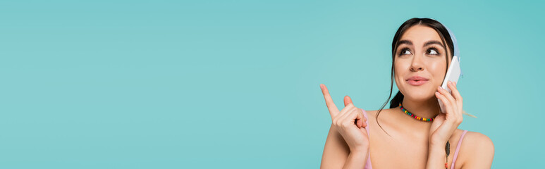 Fototapeta Young woman talking on smartphone and pointing with finger isolated on blue, banner. obraz