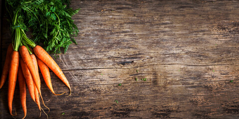 Fototapeta Top view of fresh organic carrot roots on wooden textured kitchen table. Cooking food background banner with copyspace obraz