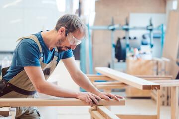 Carpenter sanding piece of wood by hand