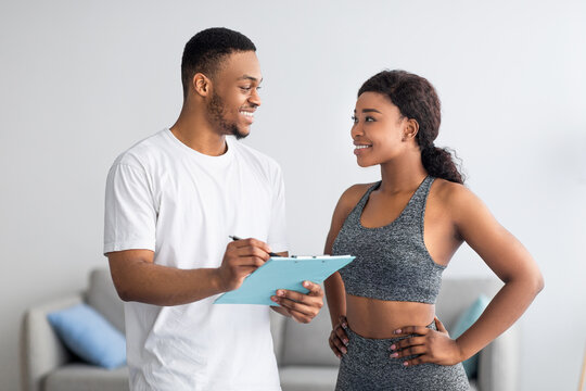 Young black couple discussing workout plan, standing together at home gym