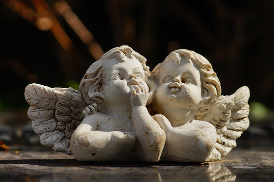 FRANKFURT, GERMANY - May 14, 2021: Two angels on a grave slab. Decoration on granite.