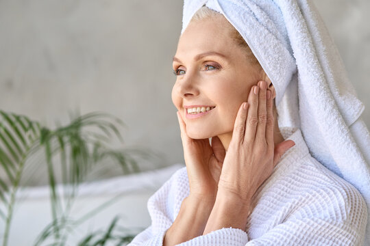 Happy smiling gorgeous middle aged woman wearing bathrobe and white towel touching face looking at window. Advertising of skin care spa wellness salon procedures concept. Closeup portrait.