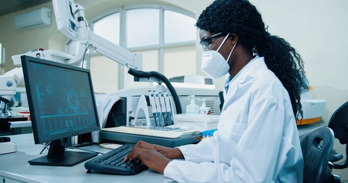 Side view of busy African American young female medical researcher sitting in lab working typing on computer looking at molecular structure developing covid cure. Modern laboratory, clinic research