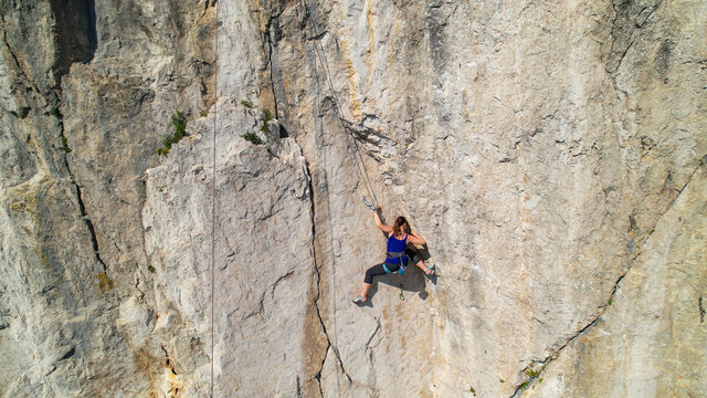 AERIAL: Drone view of a rock climber looking for a hold while learning to climb