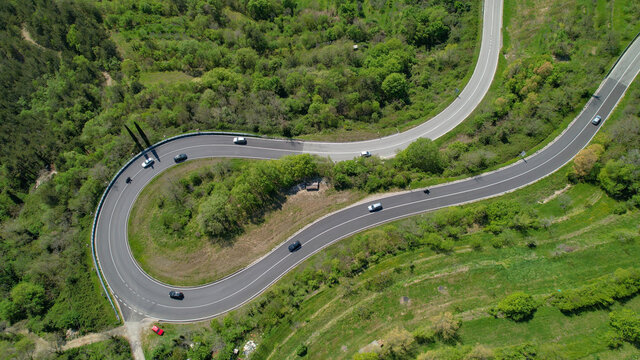 AERIAL TOP DOWN: Tourists on road trip are driving through a sharp hairpin turn.