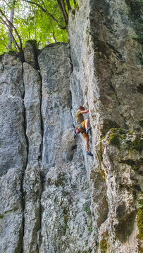 VERTICAL: Adrenaline seeking young man climbs a cliff in a tranquil forest.