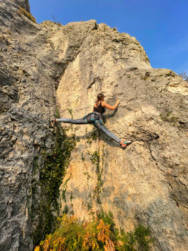 VERTICAL: Agile female rock climber almost does the splits while climbing.