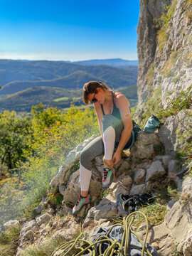 CLOSE UP Fit young woman puts on climbing shoes before rock climbing in Crni Kal