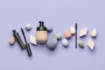 Obraz Makeup sponges with tonal foundation and mascara on color background - fototapety do salonu