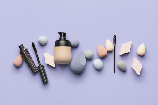Makeup sponges with tonal foundation and mascara on color background