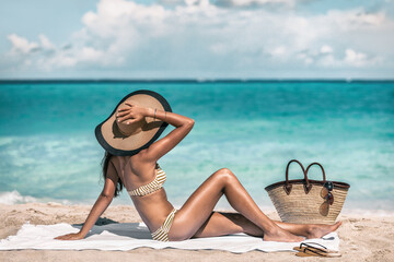 Obraz Suntan summer holiday bikini woman tanning relaxing on beach. Retro fashion lady wearing straw hat sunbathing under the Caribbean sun vacation. - fototapety do salonu