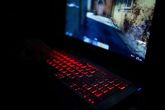 Kiev, Ukraine - June 12, 2019: Red backlit keyboard close up. Gaming laptop.