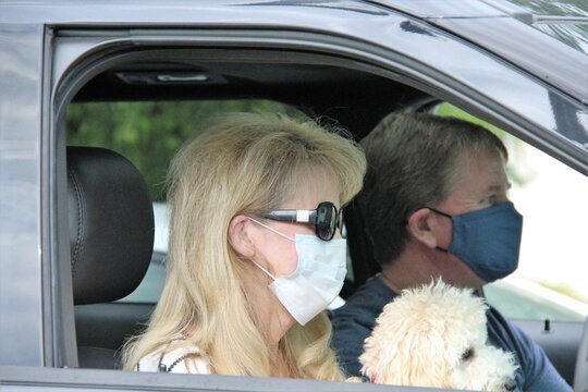 Portrait Of Young  Couple  In Car Wearing Masks