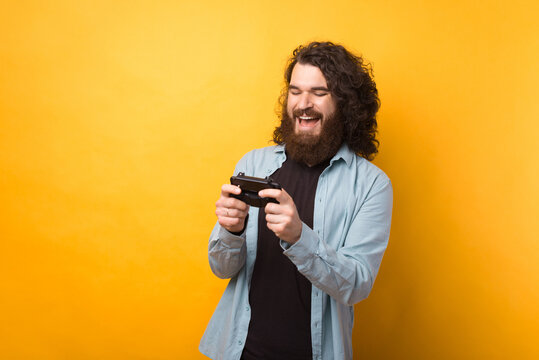 Photo of cheerful young bearded man playing games at smartphone over yellow background