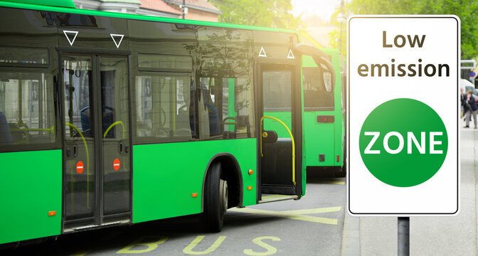 """Road sign """"Low emission ZONE"""" on a background of green buses. Clean mobility concept"""