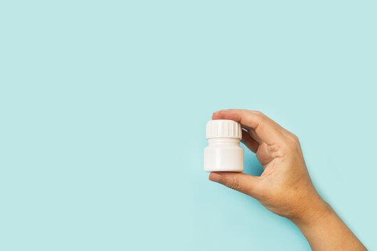 Mano de mujer sosteniendo un bote de medicamentos sobre un fondo celeste claro liso y aislado. Vista de frente. Copy space