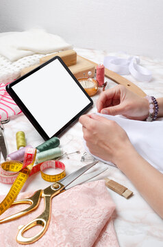 Vertical image.Woman hands who sewing and watching tutorials.Seamstress workplace, scissors, threads,digital tablet,measuring tape and other equipment for sewing