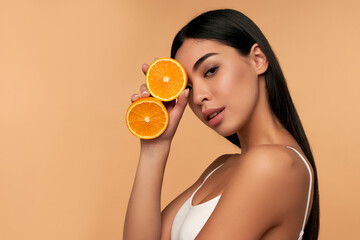Fototapeta Portrait of Asian girl with shining clean skin of face holding orange halves in white underwear isolated on beige background. Vitamin C cosmetics concept obraz