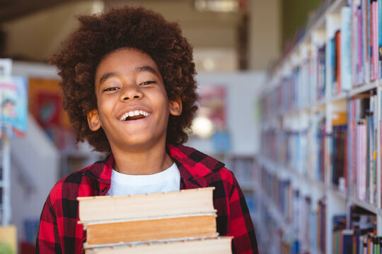 Laughing african american schoolboy carrying stack of books in school library