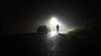 Fototapeta A lone car, parked on the side of the road, underneath a street light, with a hooded figure, on a spooky, scary, rural, country road. On a foggy winters night